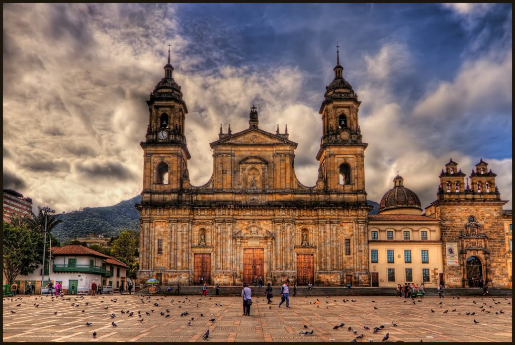 This is the main Cathedral in Bogota, Colombia, called Catedral Primada. It is in the East side of the Plaza de Bolivar. ISO 100, 15mm, f9, (1/800, 1/200, 1/50) handheld. HDR processing in Photomatix using Details Enhancer and Light mode. Imagenomics Noiseware, in PS Smart Sharpen, and Freaky Details. The warm colors came from Nik Color Efex Skylight and Indian Summer filters. I colored the sky blue using Nik Viveza 2 as Photomatix had produced the typical darkish desaturated blue. It often does this, note that the shirts of the people walking in the plaza are actually white.
