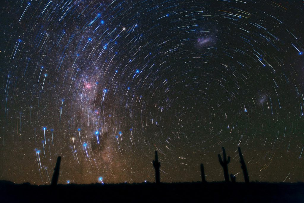 This gorgeous photograph, taken in the Atacama Desert in Chile, shows star trails circling the South Celestial Pole, over a cacti-dominated still landscape. The star trails show the apparent path of the stars in the sky as the Earth slowly rotates, and are captured by taking long-exposure shots. A final deeper exposure was superimposed over the magnificent trails, revealing many more, fainter stars and, just rising above the horizon, the southern Milky Way, with its patches of dark dust and the well-known pinkish glow of the Carina Nebula. Towards the right, the satellite galaxies of the Milky Way, the Large (top-centre) and Small (bottom-right) Magellanic Clouds, can also be seen.