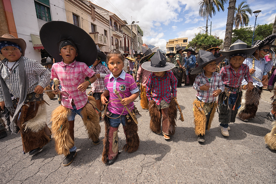 Children wearing sombreros and chaps at the Inti Raymi celebrations