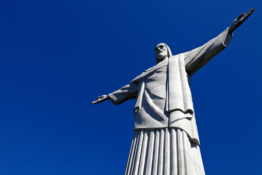 A view of Christ the Redeemer from below and underneath a blue sky.