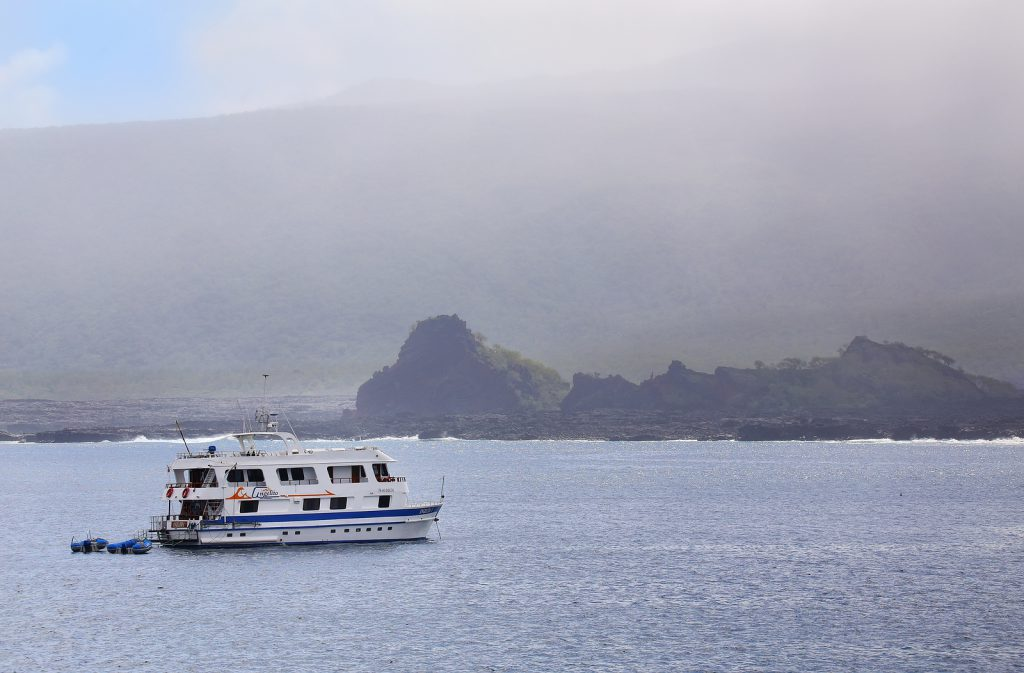 Tourist yacht anchored near Santiago Island on Galapagos National Park, Ecuador.