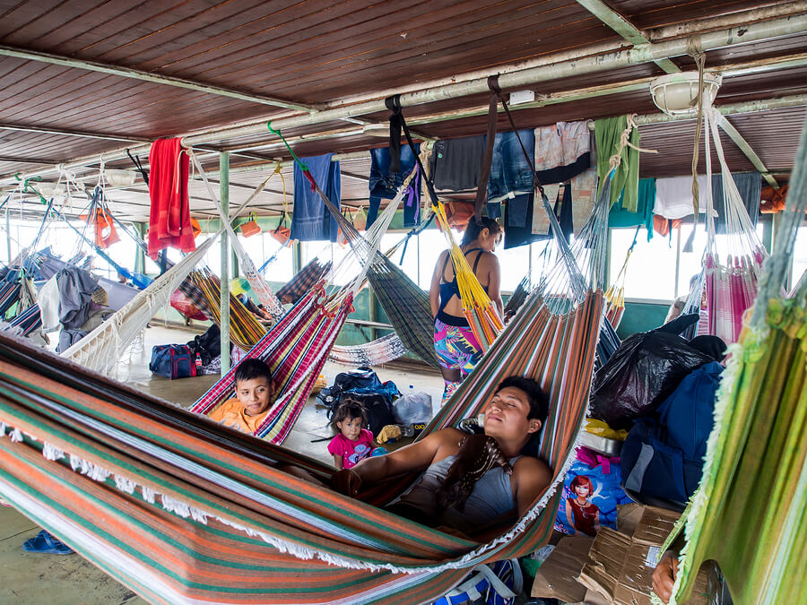 People are resting on hammocks on a deck of the cargo boat on the Amazon.