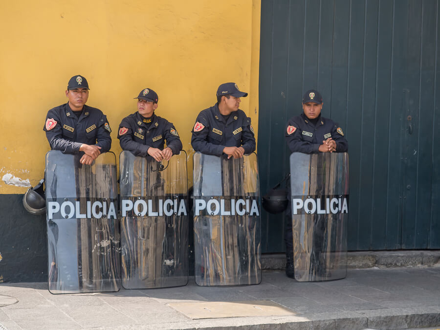 Police relax in a street in Lima.