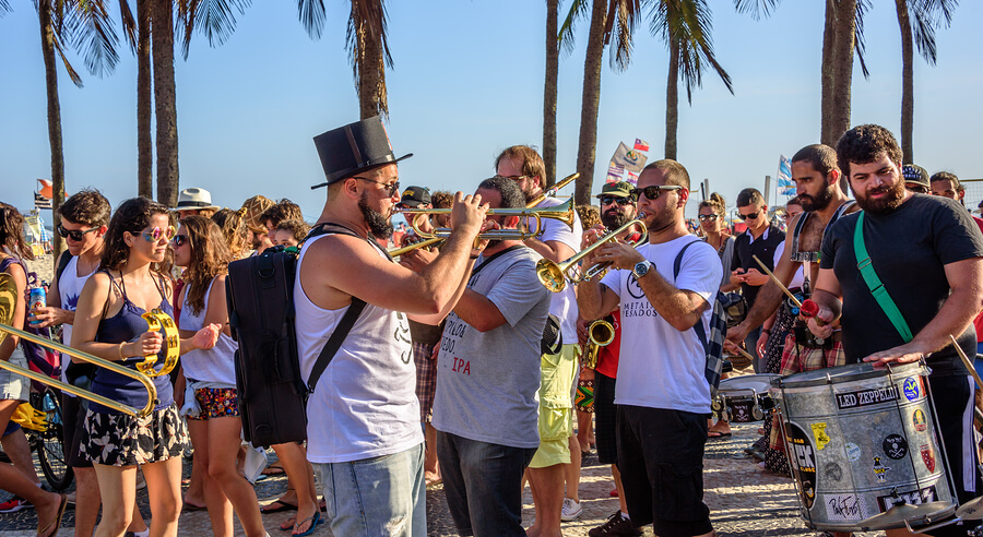 People playing music by the beach at a summer festival in Brazil.