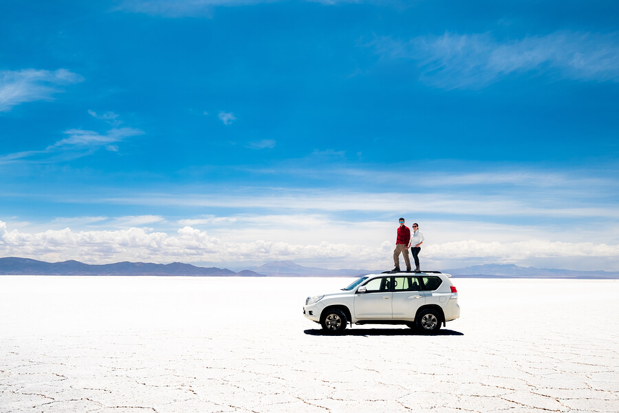 A picture of a couple standing on their car in the beautiful Salt Flats.