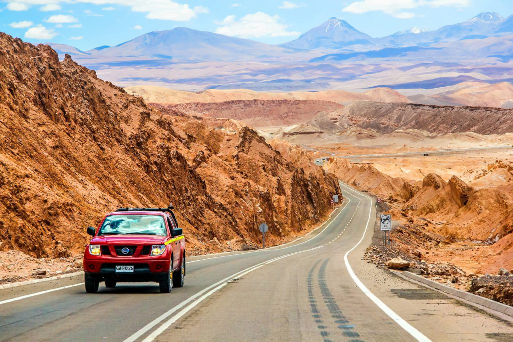 A picture of a red Nissan Navara driving through a desert in Chile.
